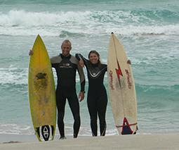 zwei Surfer stehen mit Surfbrett vor dem Meer