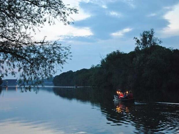 Fackelfahrt im Kanu bei Abenddämmerung