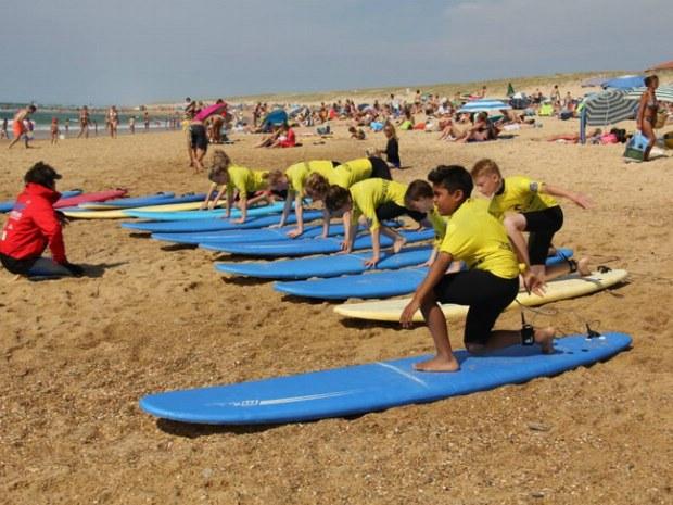 Surfkurs auf dem Surfbrett im Sand. Aufstehen