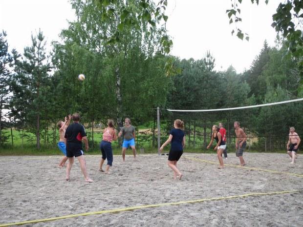 Teilnehmer spielen zusammen Beachvolleyball
