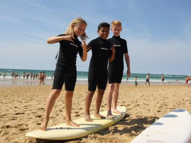 Junge Surfer machen erste Übungen auf einem Surfbrett im Sand