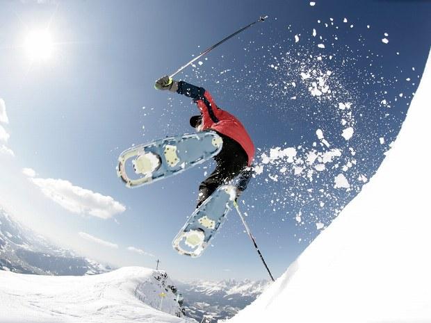 Sprung während Schneeschuhwanderung im Tiefschnee in Kitzbühel