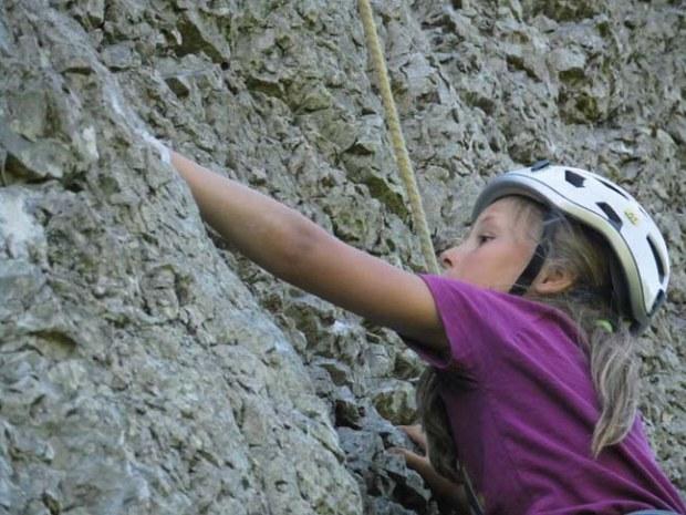 Mädchen beim Klettern an den Klippen im Familiencamp.