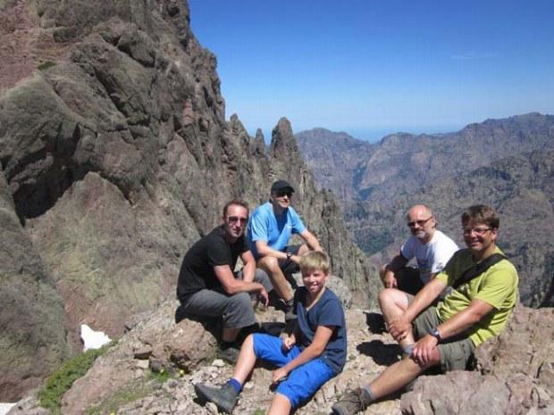 Kleine Wandergruppe machen eine Pause zwischen schroffen Felsen in Korsika