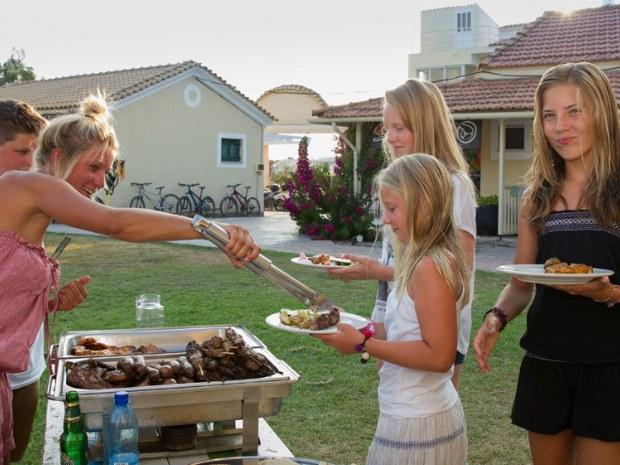 Grillabend im Sporturlaub. Mädchen holen sich Abendbrot.