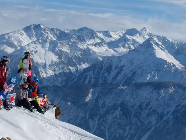 Snowboarder sitzen vor den Bergen