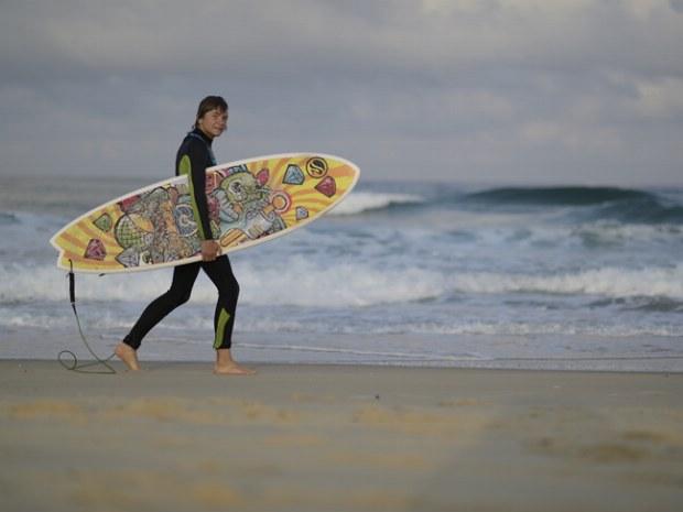 Surfer mit buntem Surfbrett unterm Arm auf dem Weg in die Wellen