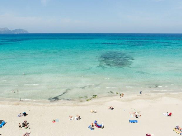 Strand mit Liegen und Sonnenschirm