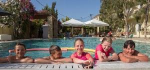 Badende Kinder im Pool lachen über den Beckenrand.