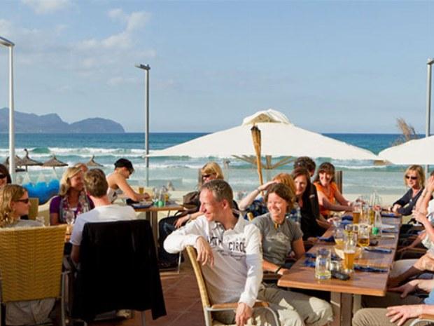 Familien sitzen zusammen beim Essen direkt am Strand