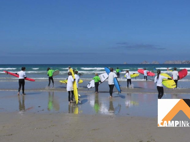 Kinder gehen während eines Surfkurs in die Wellen in der Bretagne