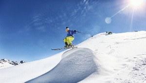 Skifahrer springt in Tiefschnee auf natürlicher Schanze in Flims-Laax