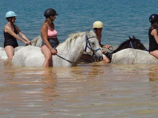 Reiter auf Pferden reiten durch den Lac de Ste. Croix. Das Wasser reicht bis zu den Knien.