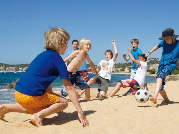 Kinder spielen Fußball am Strand des Sporthotels