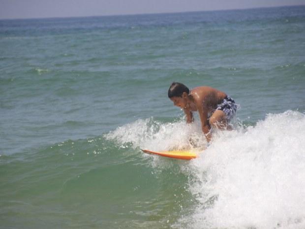 Junger Surfer surft eine kleine Welle und steht grad auf