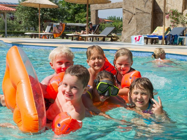Kinder spielen im Pool des Sporthotels
