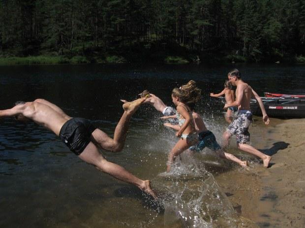 Kinder rennen in das Wasser des See.