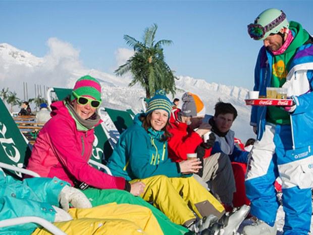Skigruppe pausiert in Liegestühlen im Skiurlaub Crans Montana in der Schweiz