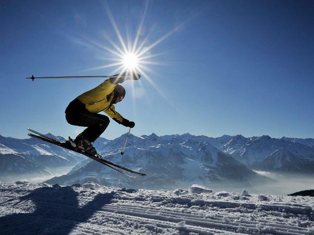 Skifahrer springt auf der Piste in Kitzbühel im Sonnenschein