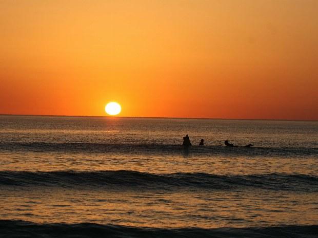 Die letzten Surfer surfen im Sonnenuntergang im Atlantik