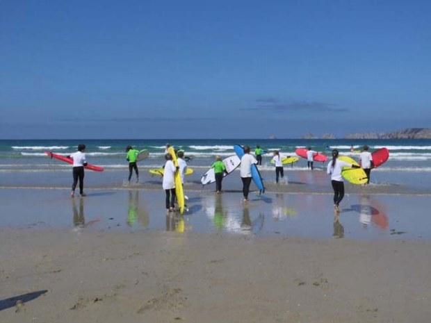 Teenager beim Surfkurs. Es geht in die Wellen am Strand im Familiencamp.
