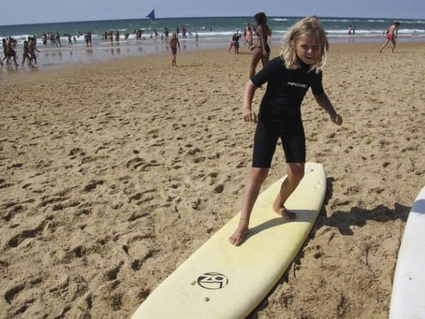 Junge Surferin testet das erste Mal ein Surfbrett im Sand