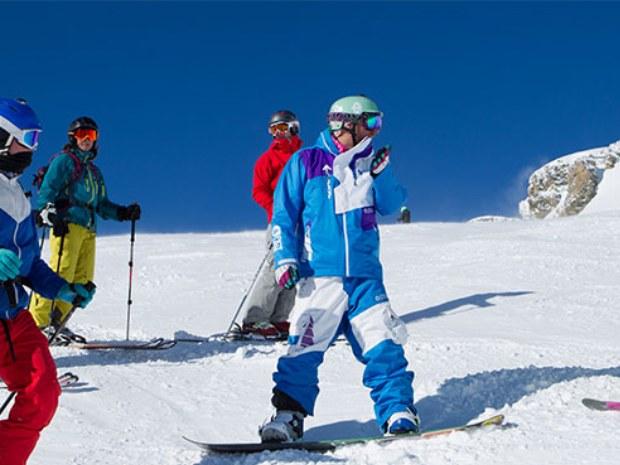Ski- und Snowboardfahrer auf der Piste im Sonnenschein im Skiurlaub in Crans Montana