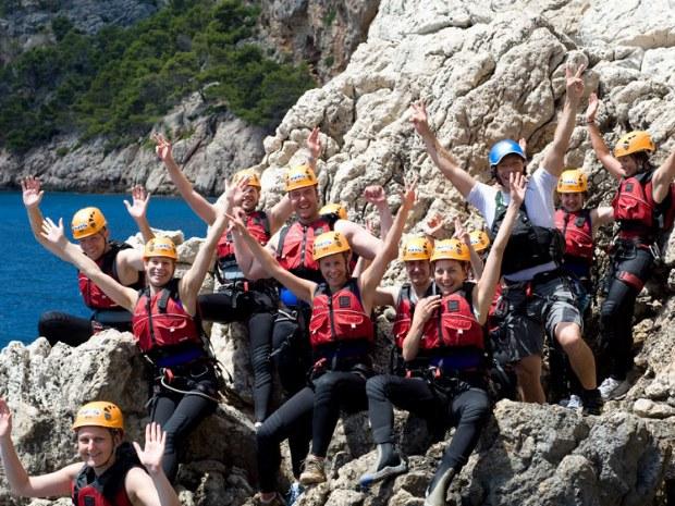 Canyoninggruppe sitzen freudestrahlend auf einem Felsen in Spanien