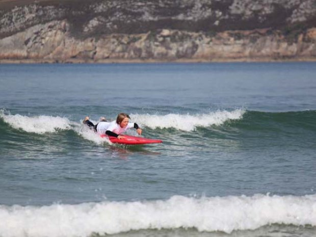 Junge liegt auf dem Surfbrett und paddelt in einer Welle