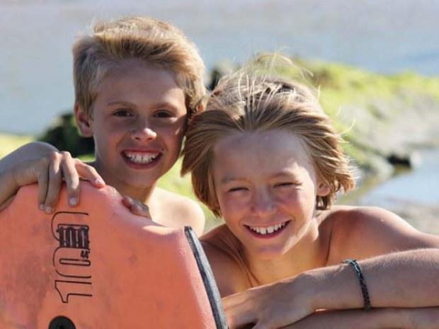 zwei Jungs freuen sich aufs Wellenreiten im Surfcamp Bretagne