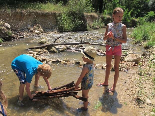 Kinder bauen Holzboote am Fluss während der Kinderbetreuung