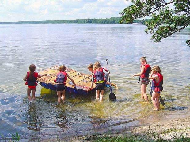 Kinder paddeln auf eigenem Floß