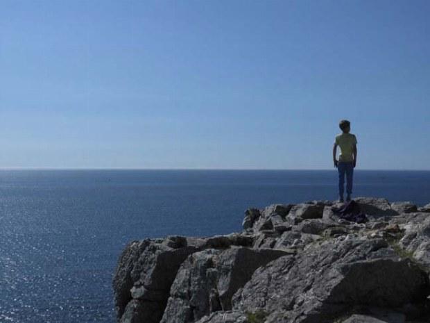 Junge genießt die Aussicht auf einer Klippe hoch über dem Atlantik