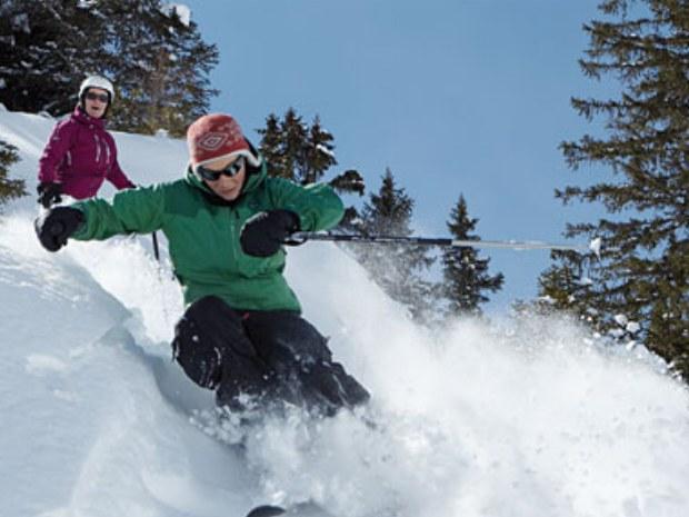 Skigruppe bei Skiabfahrt durch Tiefschnee im Skiurlaub in Champéry in der Schweiz