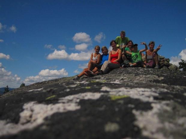 Familie pausiert auf einem Stein am Berge