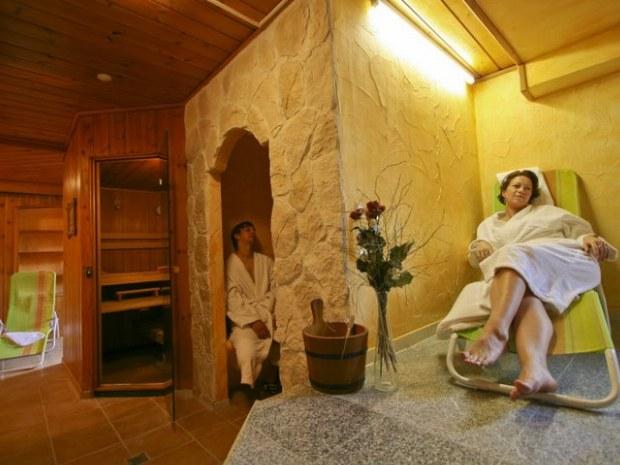In einer Sauna, zwei Personen im Bademantel.