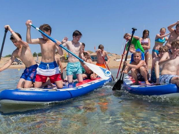 Jugendliche auf Mega-SUPs paddeln im Meer vor Korfu.