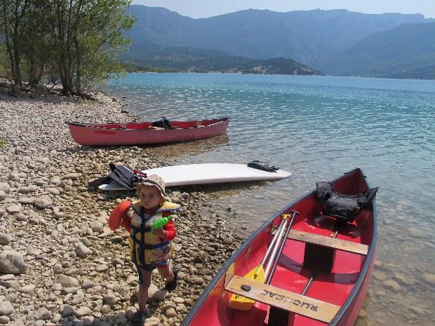 Pause einer Kanutour. Kind zwischen Kanus am Strand vom Lac de Ste. Croix.