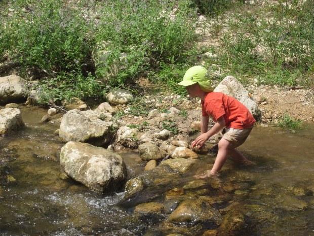 Kind im Bach beim Dammbau während der Kinderbetreuung im Urlaub