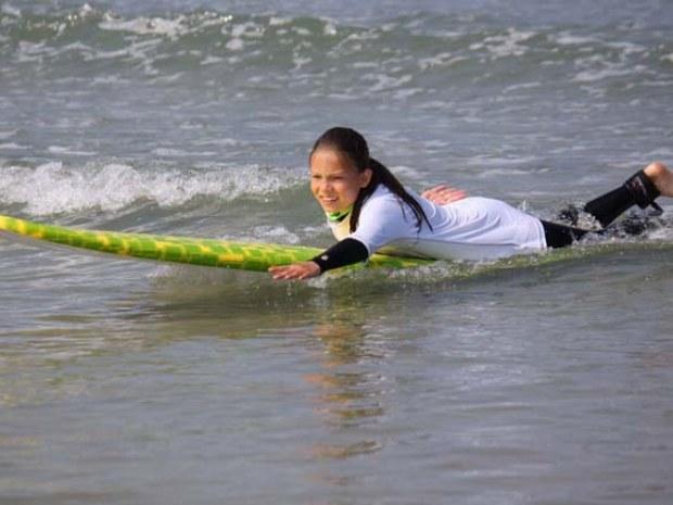 Mädchen paddelt auf dem Surfbrett liegend durch den Atlantik