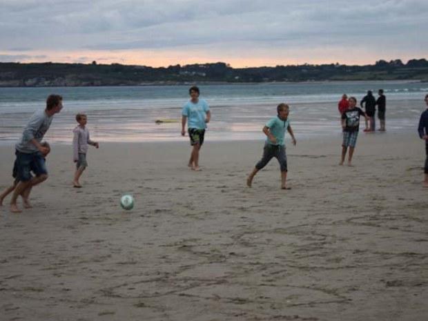 Teenager spielen in der Abenddämmerung Fußball am Strand in der Bretagne