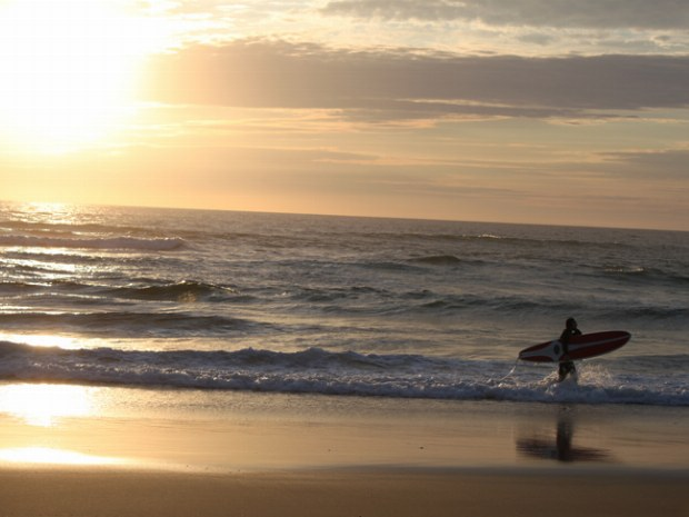 letzter Surfer verlässt bei Sonnenuntergang das Meer