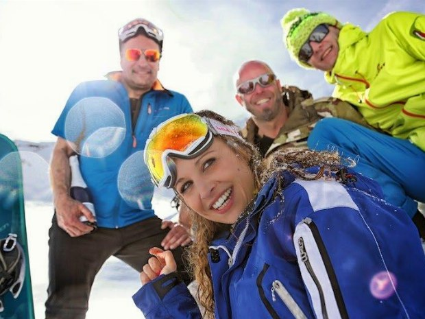 4 Skifahrer, eine Frau und drei Männer, draußen auf dem Schnee