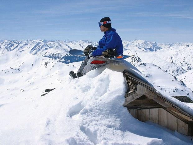 Snowboarder rastet auf Hüttendach in Skigebiet im Brixental