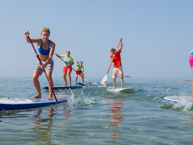 Gruppe paddelt auf dem Meer des Sportclubs
