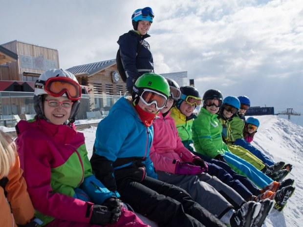 Kinder sitzen als Gruppe vor einer Skihütte