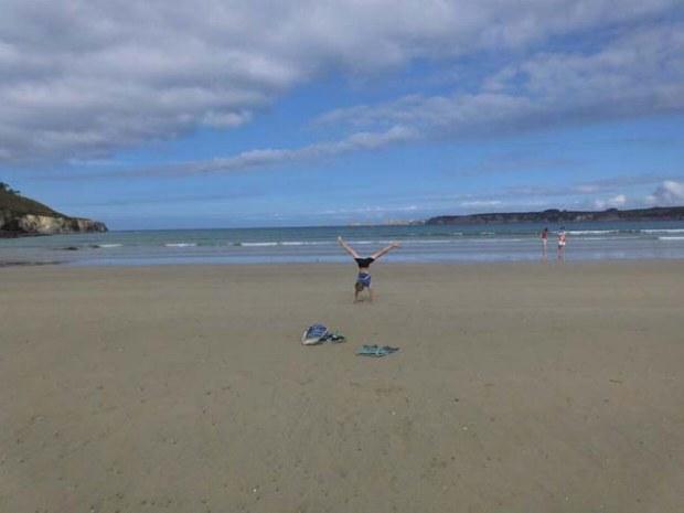 Am leeren Strand in der Bretagne macht ein Teenager einen Handstand.