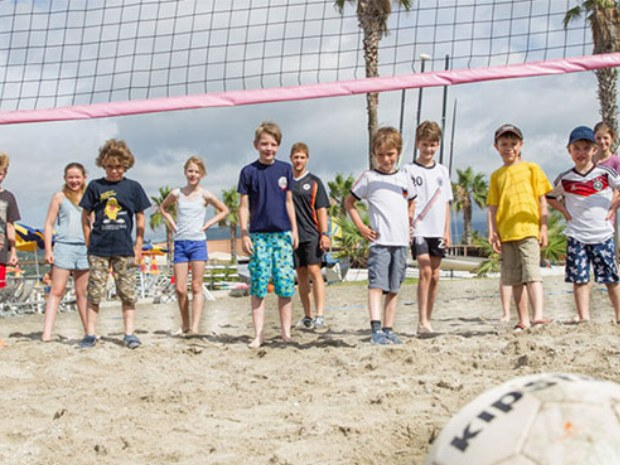 Kinder spielen am Strand Volleyball