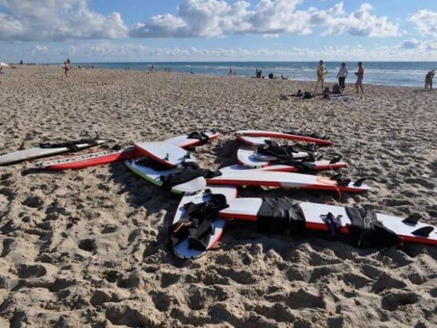 einige Surfbretter liegen im Sand und warten auf ihre Surfer
