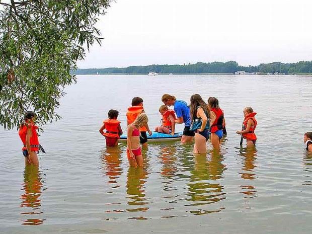 Kinder spielen im Wasser und gehen Kanu fahren